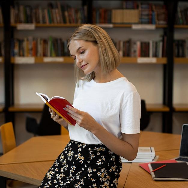 Giovane donna che studia in biblioteca Foto Gratuite