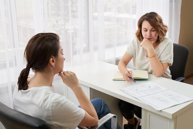 Bir masada özel öğretmenle okuyan ve not alan ve okuyan genç kadın Premium Photo