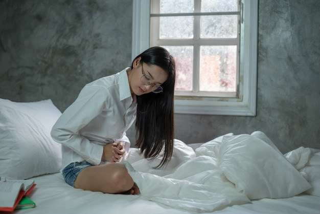 Young woman suffering from abdominal pain while sitting on bed at home Premium Photo