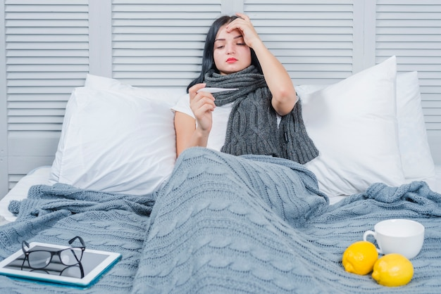 Young woman suffering from fever looking in thermometer with digital tablet; eyeglasses; lemon and cup on bed Premium Photo