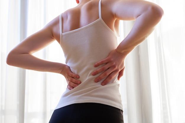 Молодая женщина страдает от боли в шее и спине, растяжения мышц. Premium Фотографии