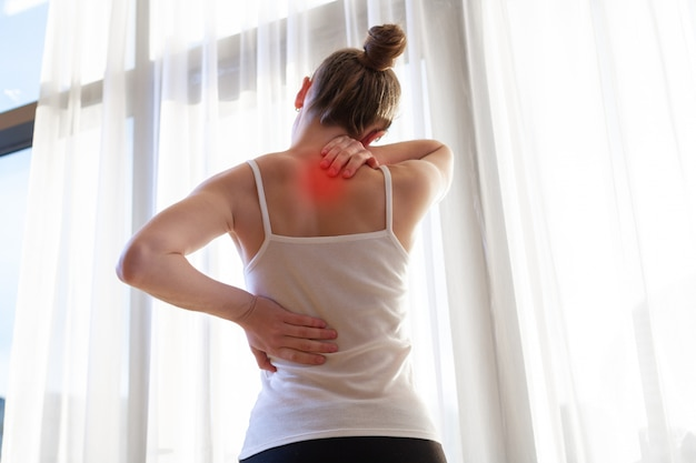 Young woman suffering from neck pain and backache, stretching the muscles at home. back and neck pain woman Premium Photo
