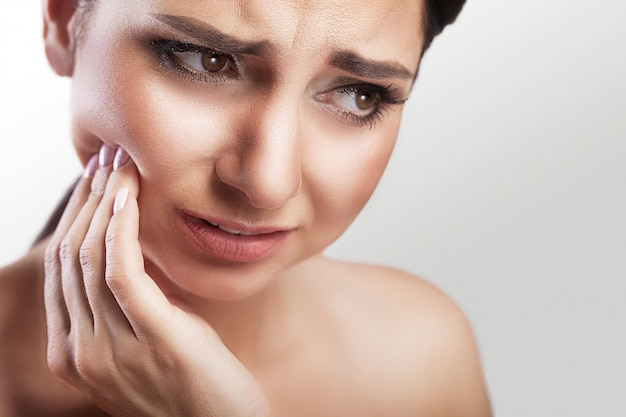 Young woman suffers from a terrible pain in her teeth Premium Photo