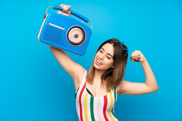 Young woman in summer holidays over blue wall holding a radio Premium Photo
