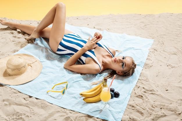 Young woman sunbathing with striped swimwear Free Photo