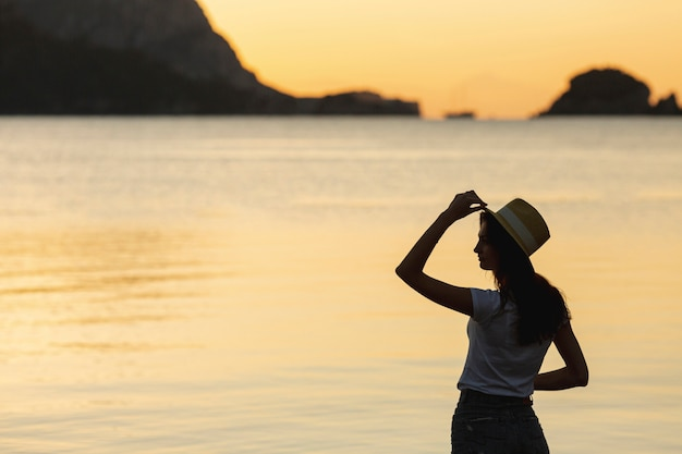 Young woman on sunset on the shore of a lake Free Photo
