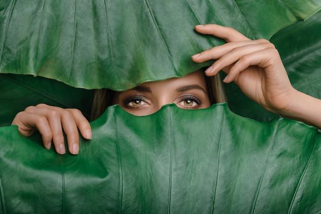 熱帯の葉に囲まれた若い女性 Premium写真