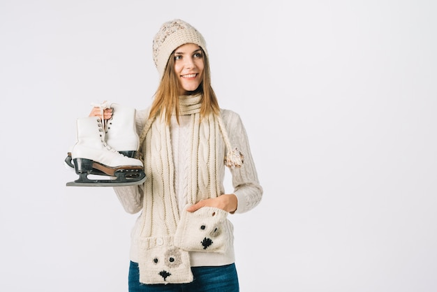 Young woman in sweater holding skates Free Photo