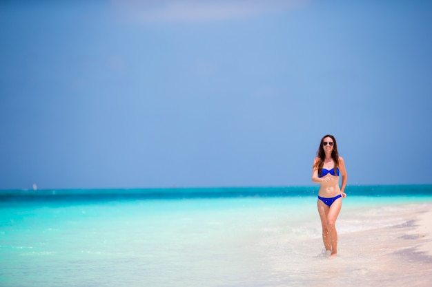 Young woman in swimsuit running and enjoying time at the beach Premium Photo
