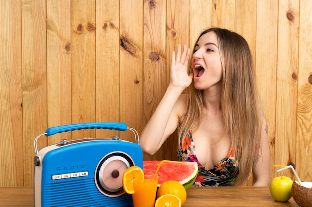 Young woman in swimsuit with lots of fruits shouting with mouth wide open Premium Photo