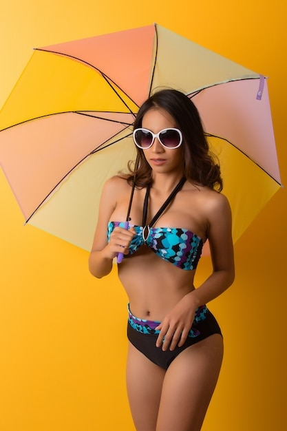 Young woman in swimwear isolated over yellow Free Photo