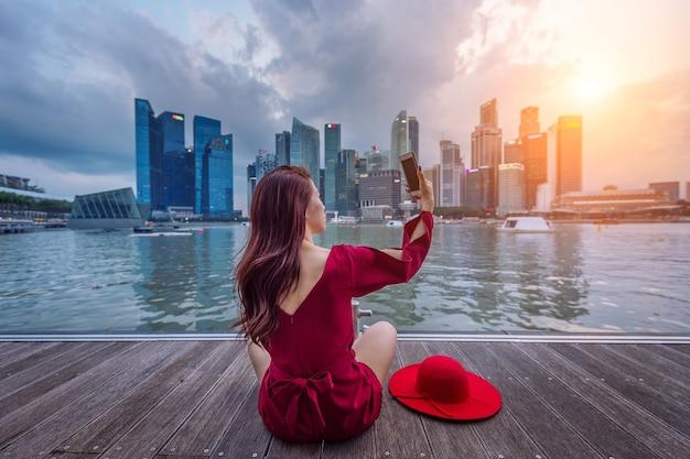 Молодая женщина фотографирует в сингапуре. Бесплатные Фотографии