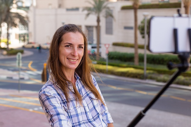 Молодая женщина делает селфи на фоне небоскребов Premium Фотографии