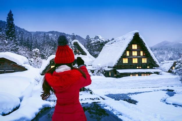 겨울, 일본 시라카와 고 마을에서 사진을 찍는 젊은 여자. 무료 사진