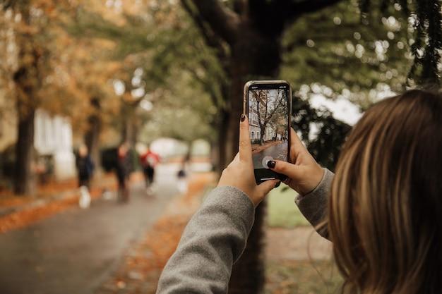 스마트 폰으로 사진을 찍는 젊은 여자 무료 사진