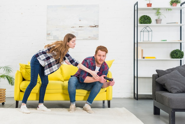 Young woman taking joystick from his boyfriend playing the video game Free Photo