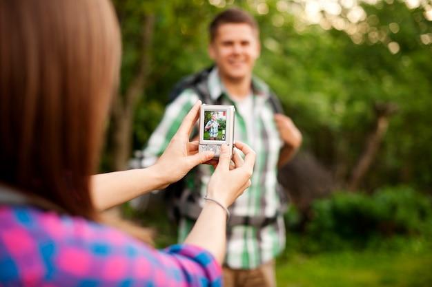 彼女のボーイフレンドのために写真を撮る若い女性 無料写真
