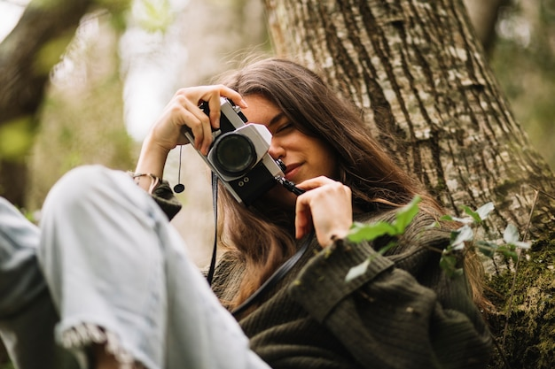 Young woman taking photo in nature Free Photo