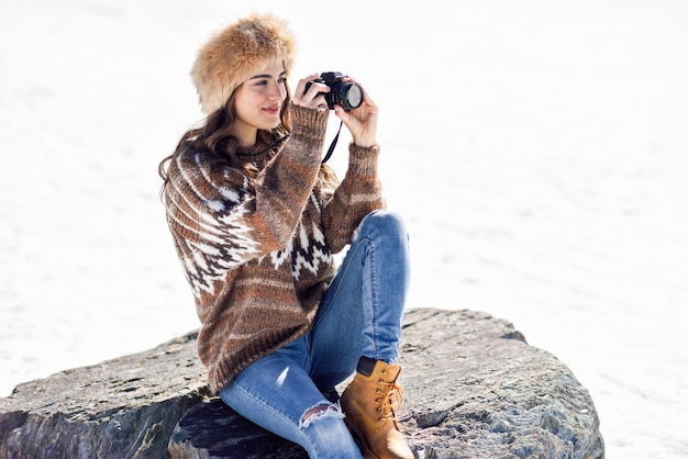 Young woman taking photographs in the snowy mountains Premium Photo
