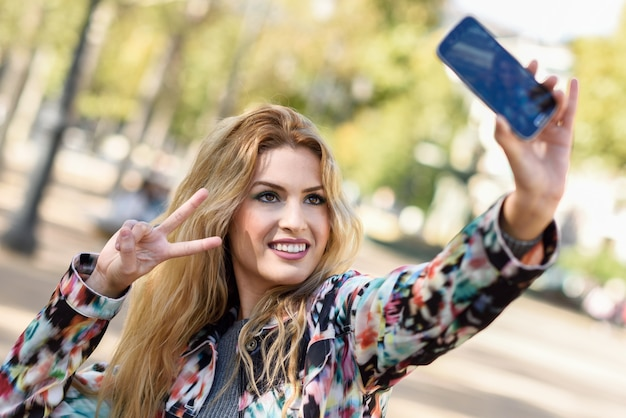 Young woman taking selfie and showing victory gesture Free Photo