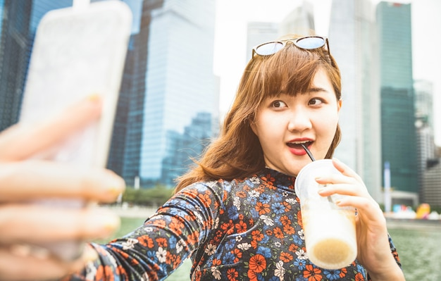 Young woman taking selfie with coffee in singapore Premium Photo