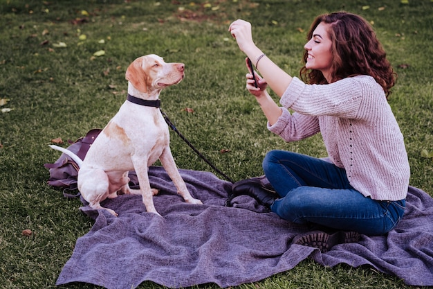 Young woman taking a selfie with mobile phone with her dog at the park Premium Photo