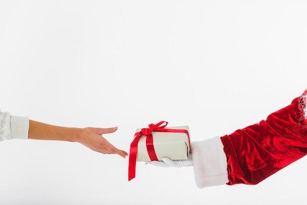 Young woman taking small gift box at santa claus Free Photo