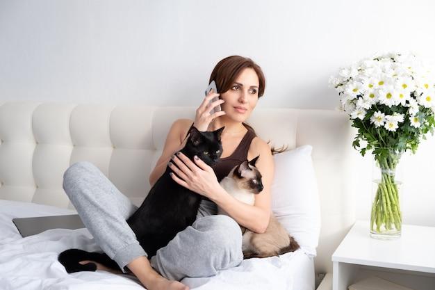 花と白い寝室で彼女の2匹の猫と電話で話している若い女性。 Premium写真