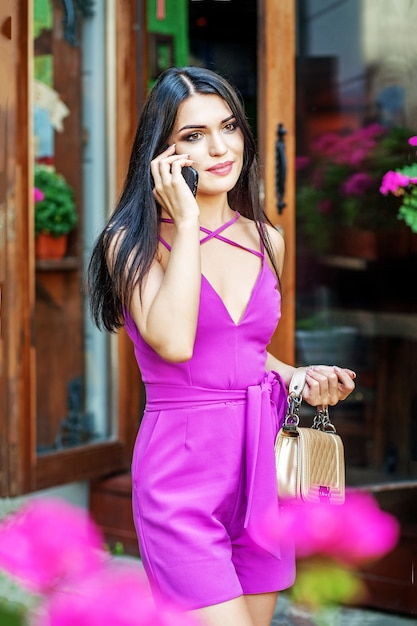 Молодая женщина разговаривает по улице на телефоне. Premium Фотографии