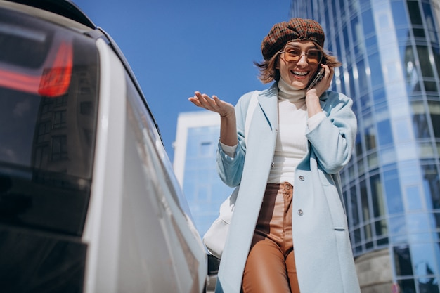 Young woman talking on the phone by electro car in the center Free Photo