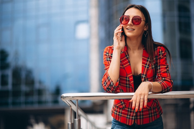 Young woman talking on the phone by the office center Free Photo
