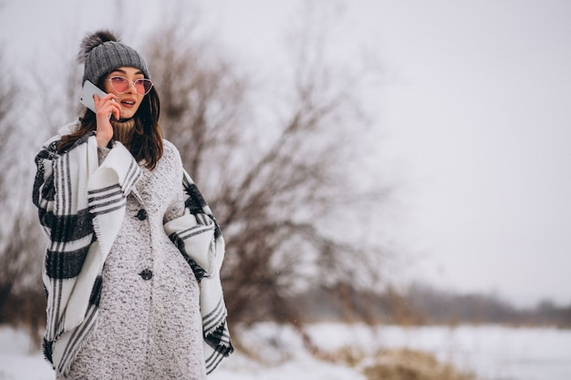Young woman talking on phone outside in winter park Free Photo