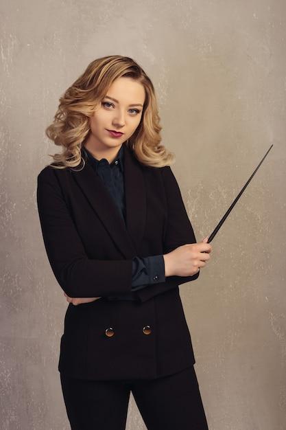 Учитель молодой женщины с указателем в руке около серой текстурированной стены. Premium Фотографии