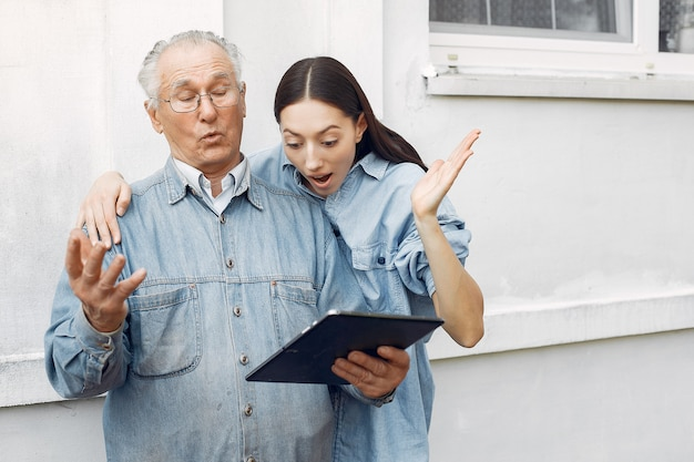 Young woman teaching her grandfather how to use a tablet Free Photo