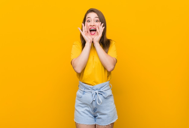 Young woman teenager wearing a yellow shirt shouting excited to front. Premium Photo