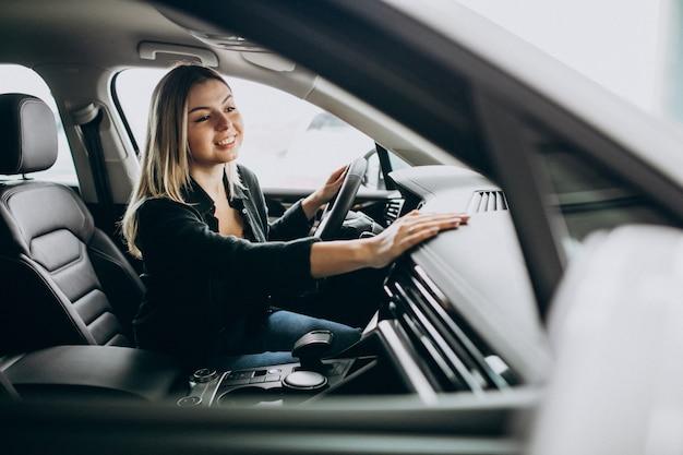 Giovane donna che collauda un'automobile in una sala d'esposizione dell'automobile Foto Gratuite