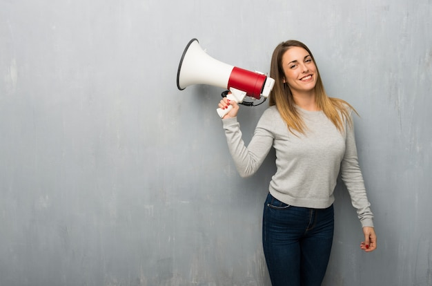 Young woman on textured wall holding a megaphone Premium Photo
