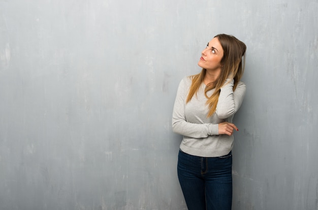Young woman on textured wall thinking an idea while scratching head Premium Photo