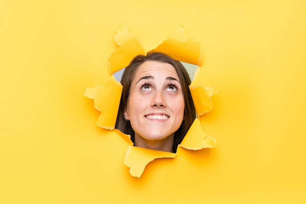 Young woman through a hole paper looking up Premium Photo