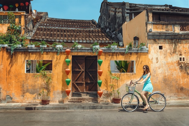 A young woman tourist  in a blue short dress rides a bicycle along the street of the vietnamese tourist city of hoi an. cycling through the old town of hoi an Premium Photo