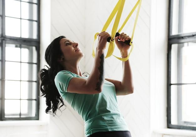 ジムでトレーニングする若い女性 無料写真