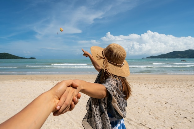 Young woman traveler holding man's hand and looking parachute flying in the sky on the beach Premium Photo