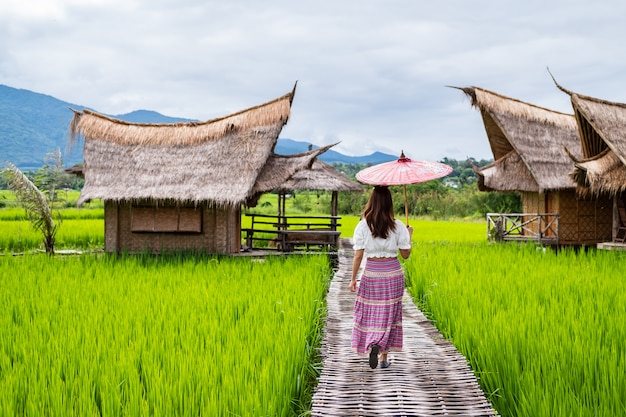 Young woman traveler looking and relaxing with beautiful green paddy field Premium Photo
