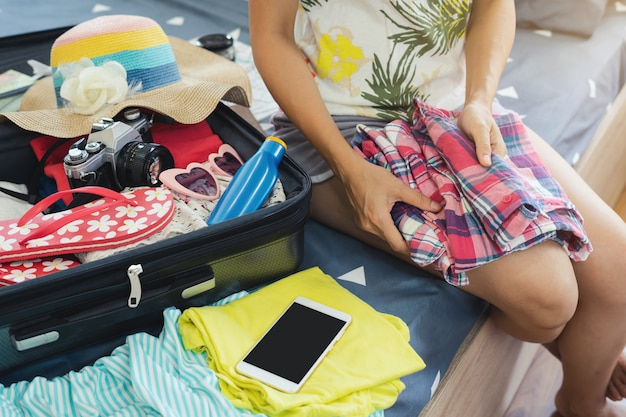 Young woman traveler packing her clothes and stuff in suitcase Premium Photo