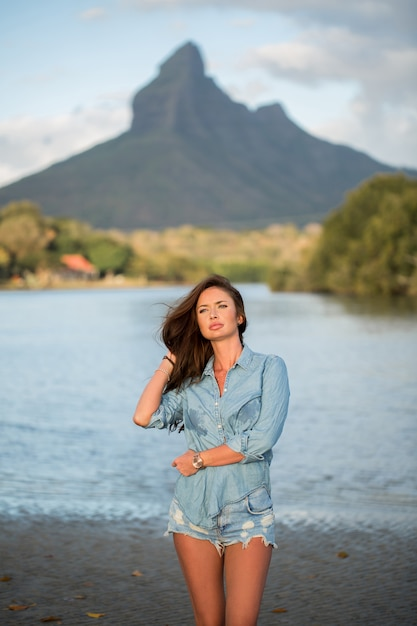 Young woman traveler stands on the beach against the mountain and enjoy the beauty of the sea landscape. young woman loves wild life, travel, freedom. Premium Photo