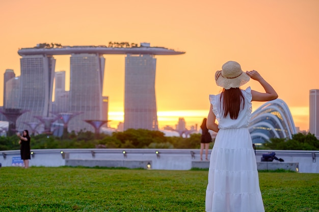Young woman traveling with hat at sunset, happy asian traveler visit in singapore city downtown. landmark and popular for tourist attractions. asia travel concept Premium Photo