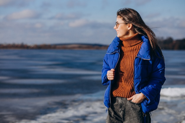 Young woman traveller in blue jacket looking the sea Free Photo