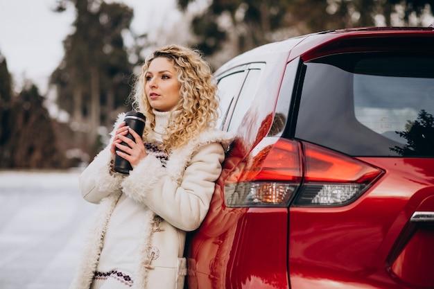 Giovane donna che viaggia con la macchina e si ferma su una strada piena di neve per bere un caffè Foto Gratuite