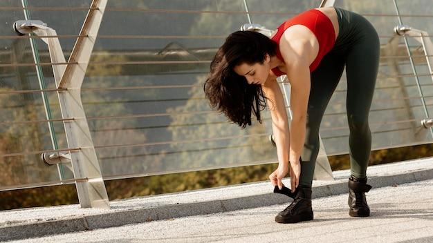 Giovane donna che lega i suoi lacci delle scarpe Foto Gratuite