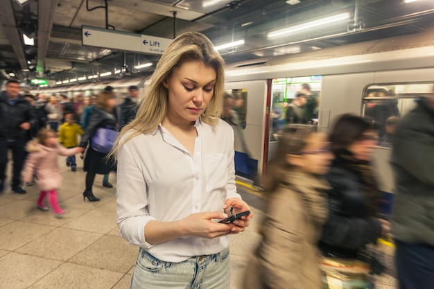 Young woman typing on smart phone at tube station Premium Photo